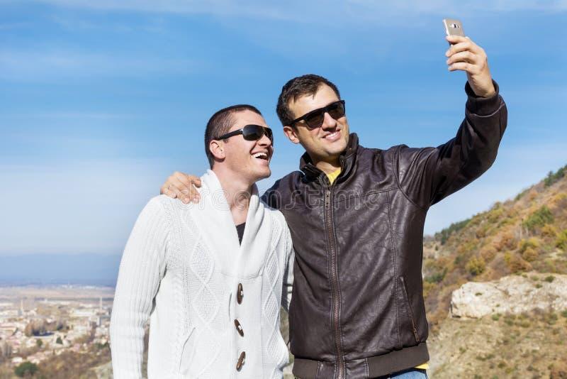 做在山的两个微笑的年轻人画象selfi 库存照片