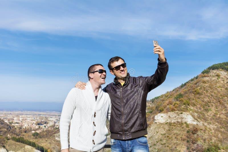 做在山的两个微笑的年轻人画象selfi 免版税库存图片