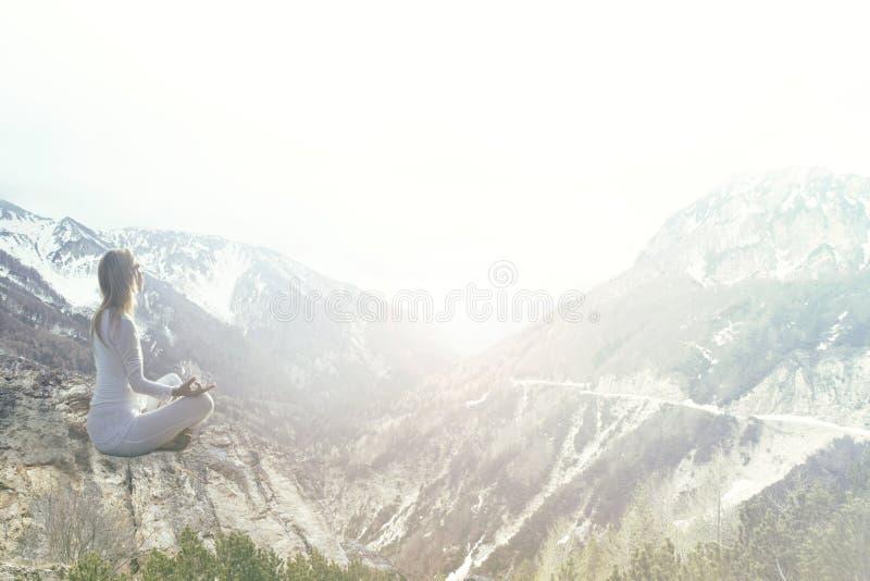 做在山的妇女瑜伽 图库摄影