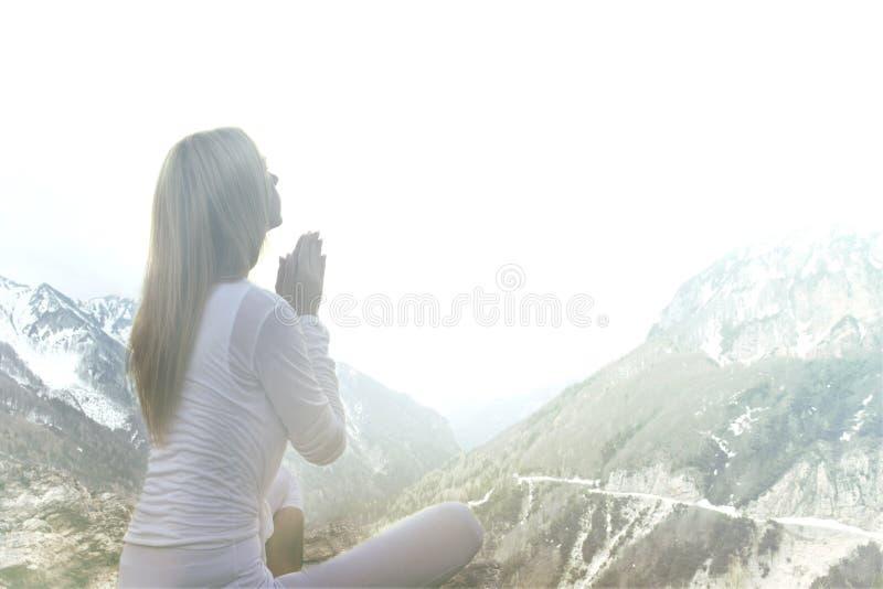 做在山的妇女瑜伽 库存图片