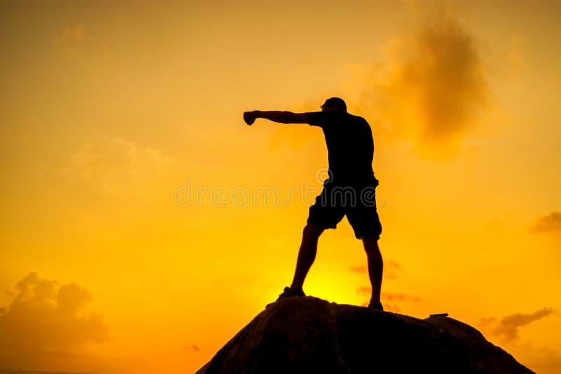 做在岩石的一个人的剪影锻炼 库存图片