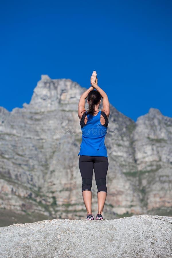 做在岩石的夫人瑜伽 图库摄影