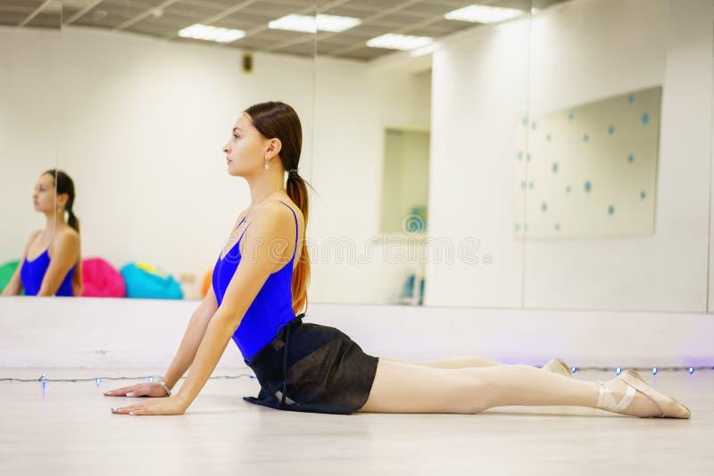 做在席子的年轻女人准备在健身房 图库摄影