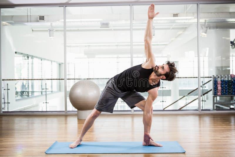 做在席子的英俊的人瑜伽 免版税图库摄影