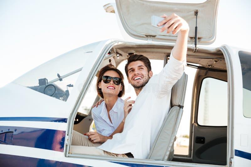 做在平面客舱里面的愉快的微笑的夫妇selfie 免版税库存照片