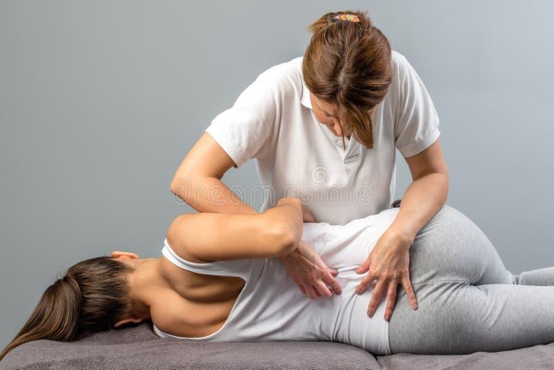 做在患者的女性治疗师整骨疗法脊椎治疗 库存照片