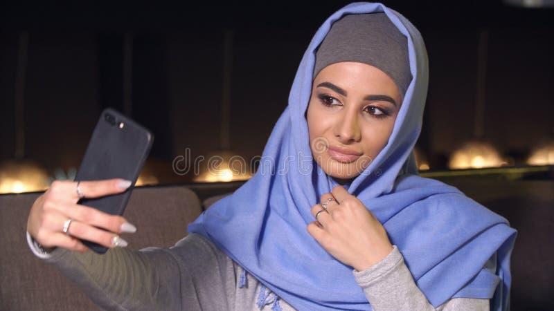 做在手机照相机的hijab的年轻美丽的妇女selfie 回教妇女和现代技术 库存图片
