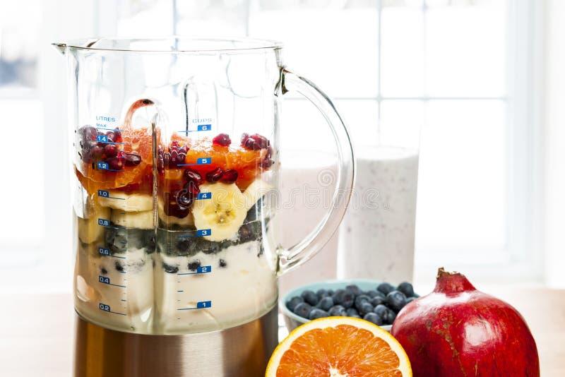 做在搅拌器的圆滑的人用果子和酸奶 库存照片