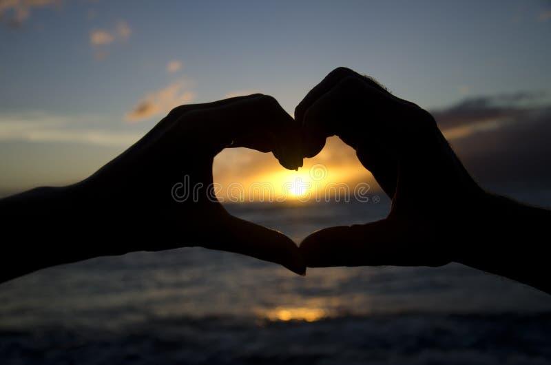 做在日落的两只手心脏 免版税库存照片