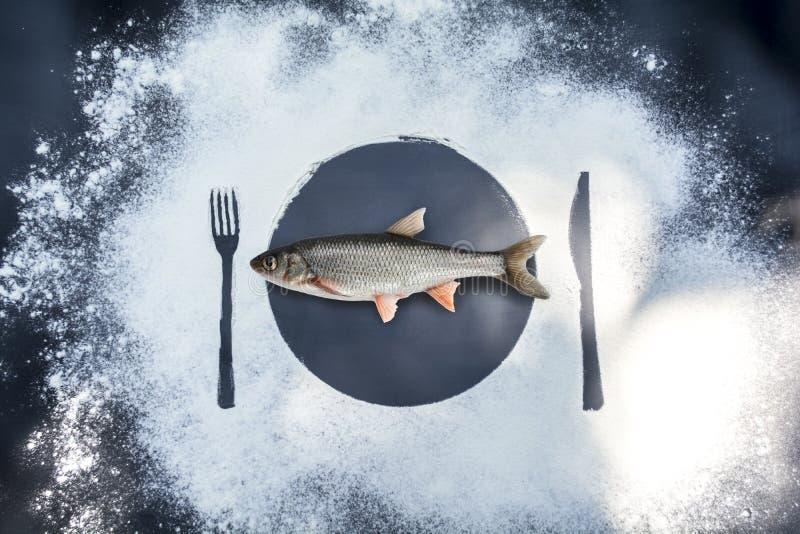 做在早晨日出的饵料 在黑大理石背景用用剪影板材叉子刀子和鱼盖的面粉 免版税库存图片