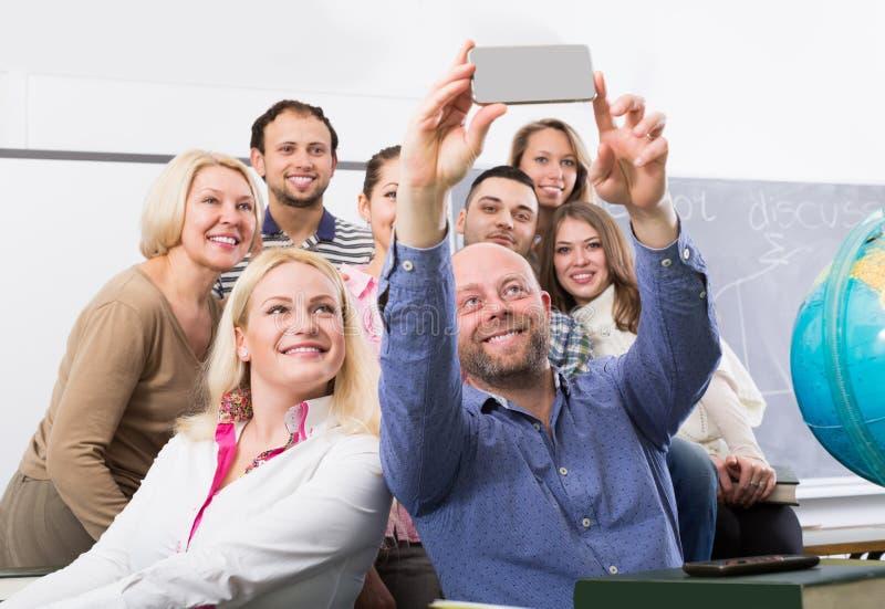 做在智能手机的另外年龄的学生小组selfie 库存照片