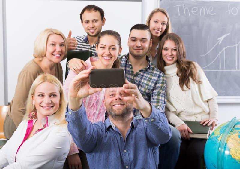 做在智能手机的另外年龄的学生小组selfie 库存图片