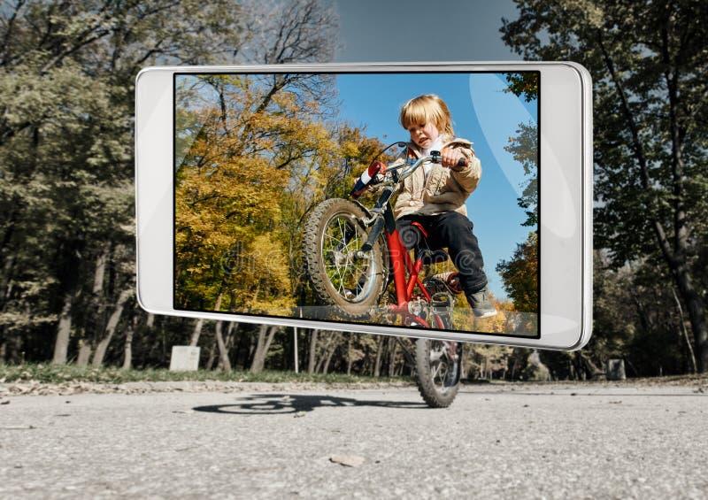 做在智能手机的小男孩一个把戏 免版税图库摄影