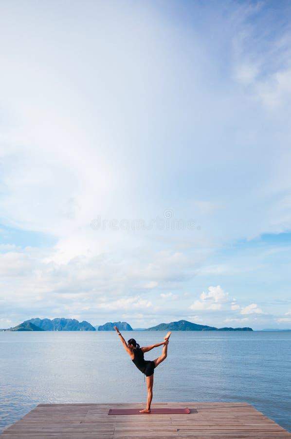 做在木码头的亚裔妇女瑜伽由海 酸值lanta,甲米府,泰国 免版税库存图片
