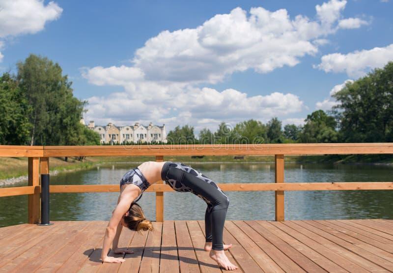 做在桥梁的灰色体育穿戴的年轻亭亭玉立的女孩瑜伽 有红色头发的灵活的女孩 库存图片
