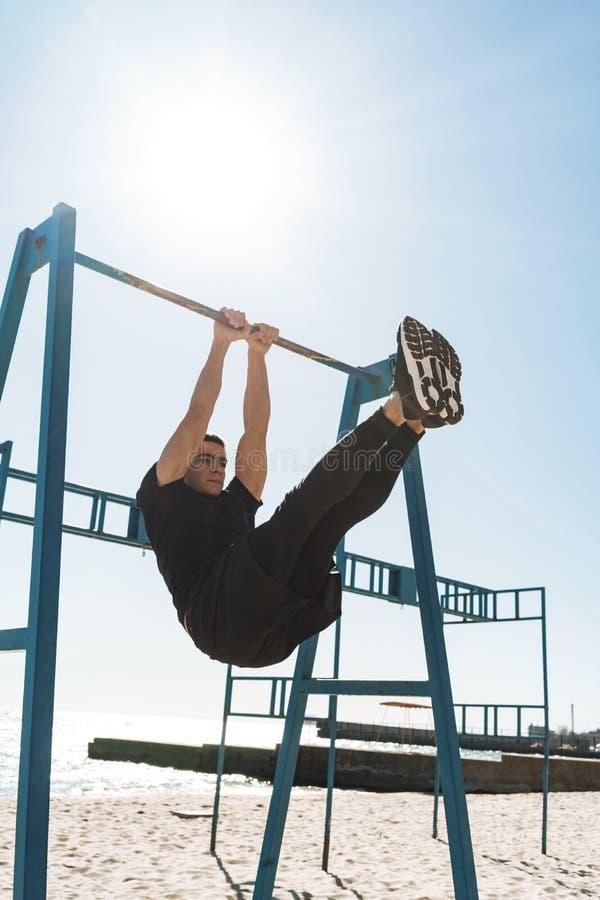 做在水平的体操酒吧的帅哥照片杂技在早晨锻炼期间由海边 库存图片