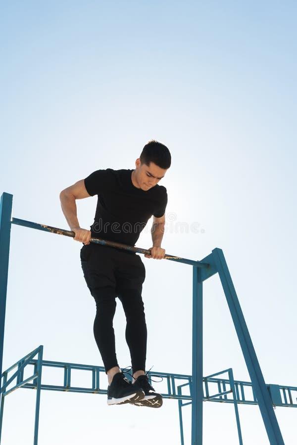 做在水平的体操酒吧的精力充沛的人照片杂技在早晨锻炼期间由海边 库存照片