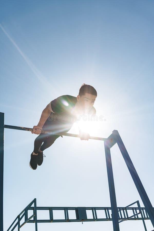 做在水平的体操酒吧的运动运动员照片杂技在早晨锻炼期间由海边 免版税库存照片