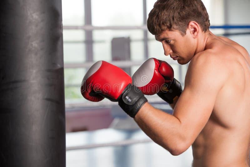 做在沙袋的拳击手一些训练在健身房 库存图片