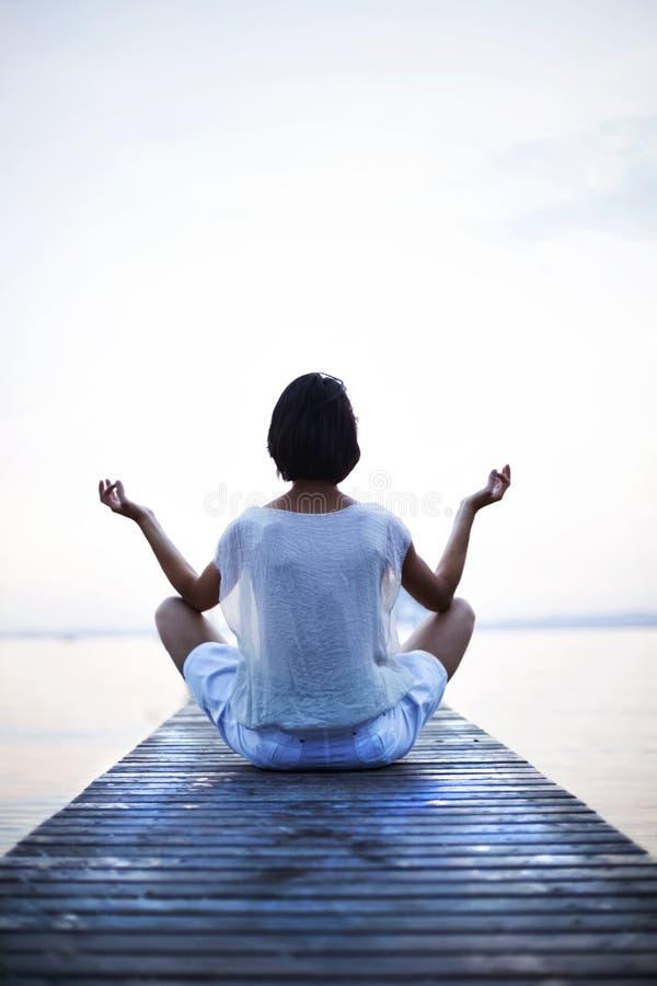 做在海前面的凝思妇女瑜伽 免版税库存图片