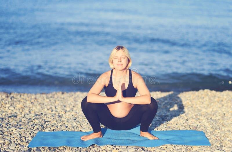 做在海岸的一名怀孕的亚裔妇女的画象瑜伽 库存图片