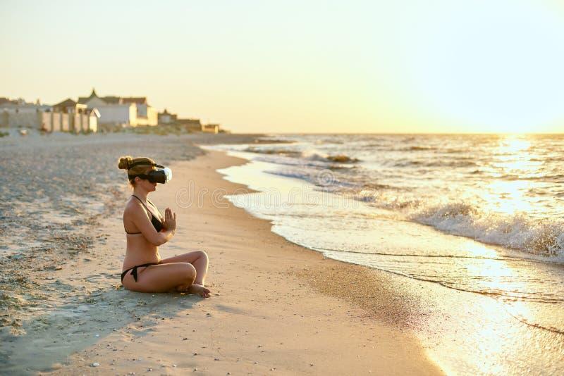 做在海洋海滩的VR玻璃的妇女瑜伽padmasana早晨 使用虚拟现实的女孩为深刻的浸没 库存照片