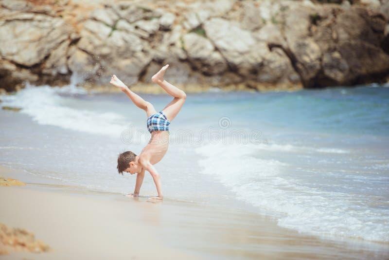 做在海海浪的男孩一个车轮 图库摄影