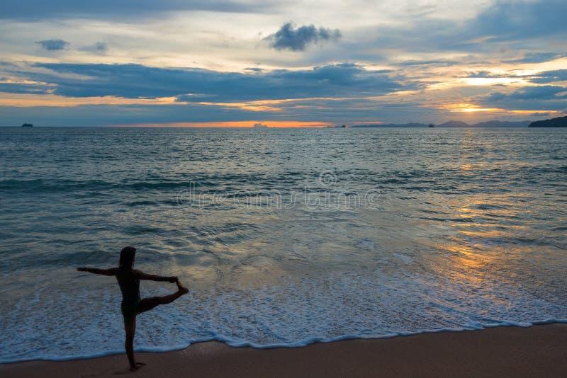 做在海滩的活跃妇女瑜伽在日落 图库摄影