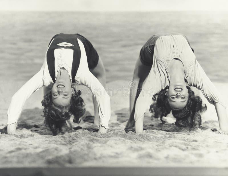 做在海滩的两名妇女桥 库存图片