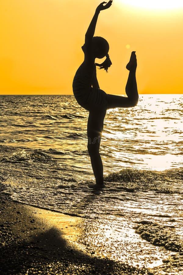 做在海滩的女孩杂技在日落 免版税库存照片