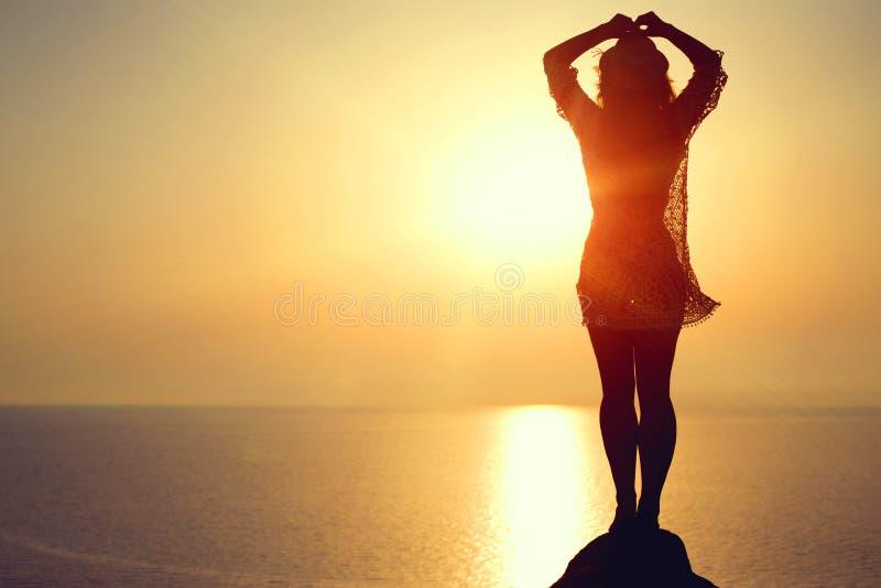 做在海滩的妇女瑜伽形象在日落 库存照片