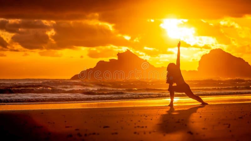 做在海滩的少妇剪影瑜伽 免版税图库摄影