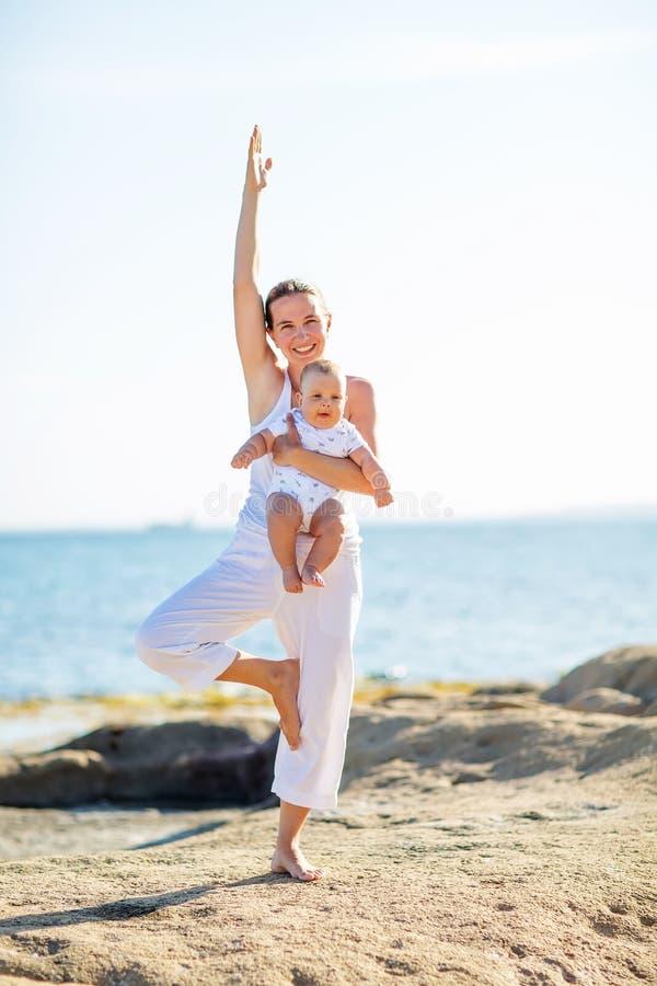 做在海滩的母亲和儿子锻炼 图库摄影