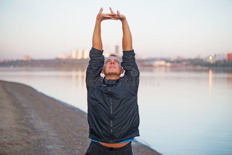 做在海滩的运动人锻炼在日落户外 免版税库存图片