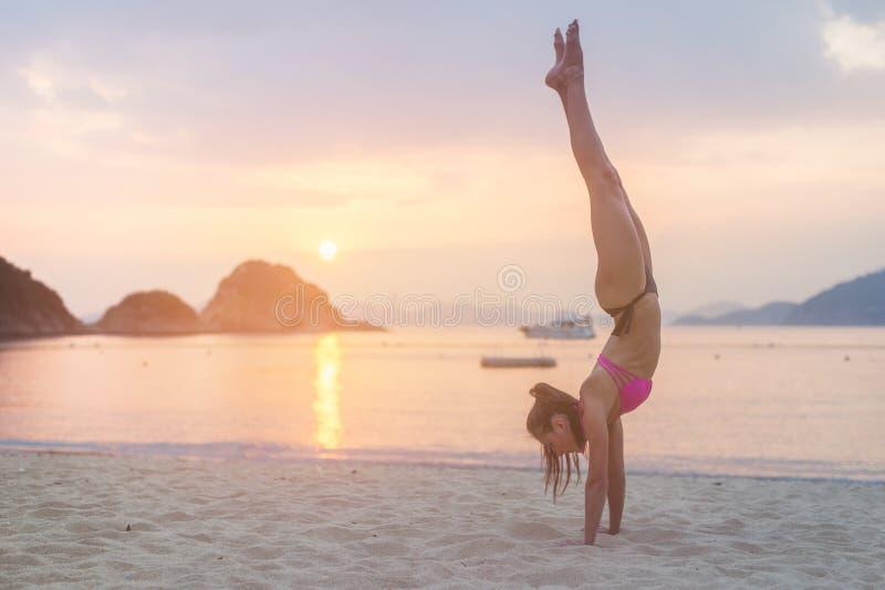 做在海滩的年轻健身妇女手倒立锻炼在日出 比基尼泳装实践的瑜伽海滨的运动的女孩 库存图片