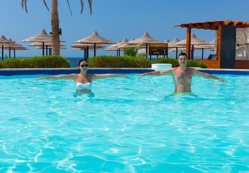 做在游泳池的愉快的年轻夫妇水色健身 库存照片