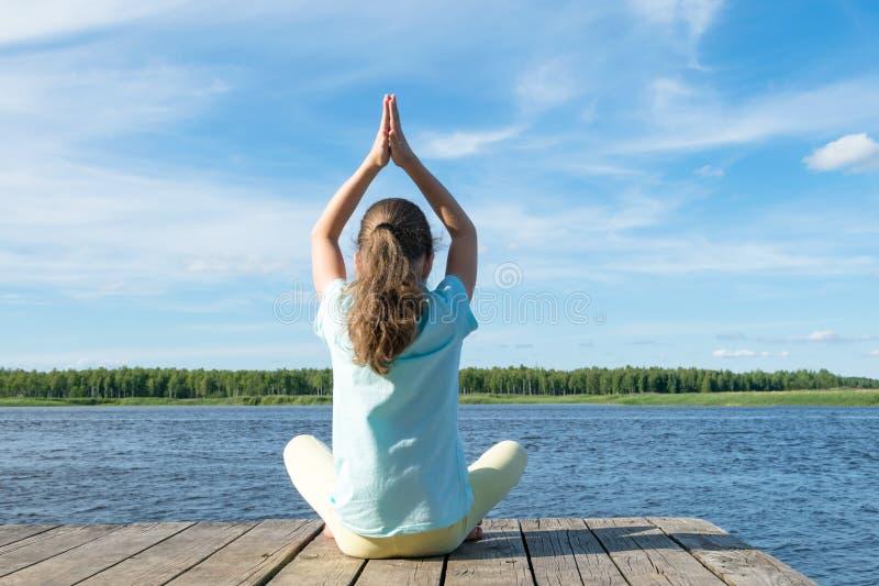 做在湖的岸的女孩早晨运动在一好日子,背面图 免版税图库摄影