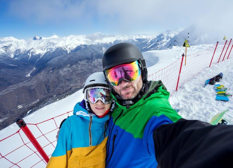 做在照相机的夫妇挡雪板selfie 库存图片