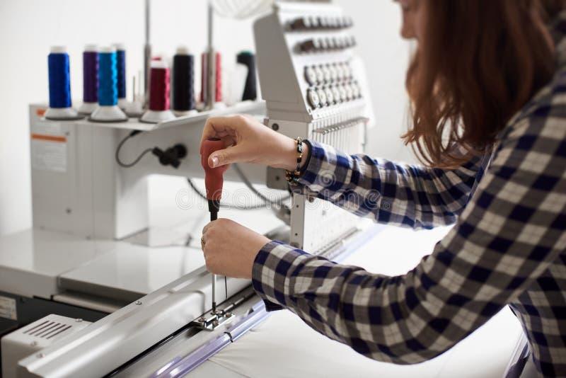 做在现代计算机化的刺绣机器的妇女操作员调整使用螺丝刀 免版税库存图片