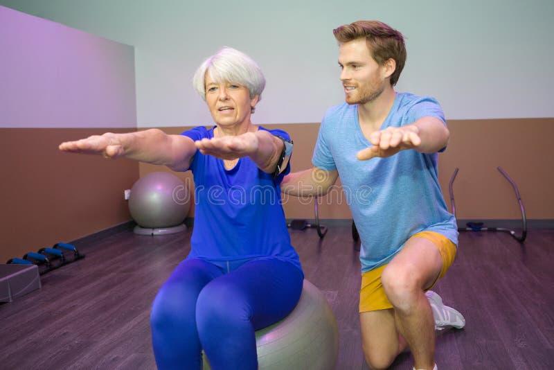做在球的老妇人物理疗法 免版税库存图片