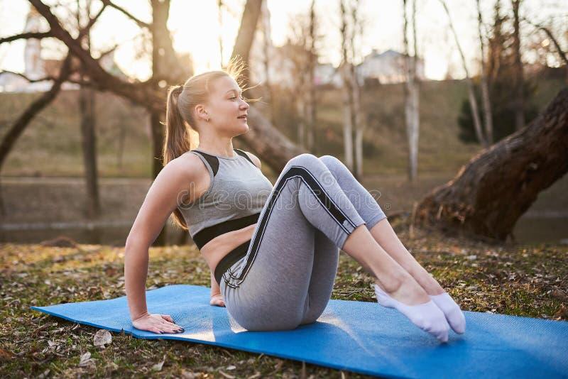 做在瑜伽席子的女孩瑜伽在公园 库存图片