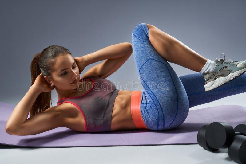 做在瑜伽席子的被晒黑的年轻运动女孩吸收锻炼 库存照片