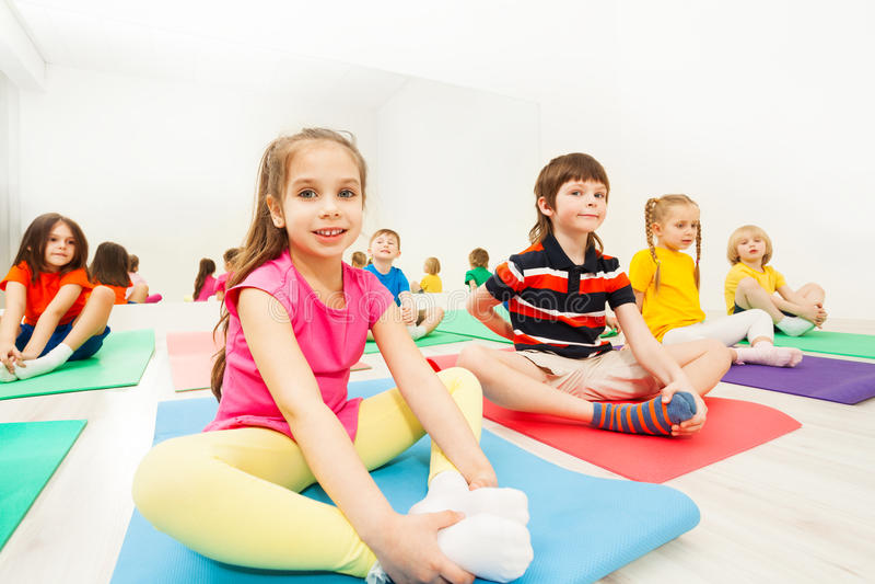 做在瑜伽席子的运动的女孩蝴蝶舒展 库存图片