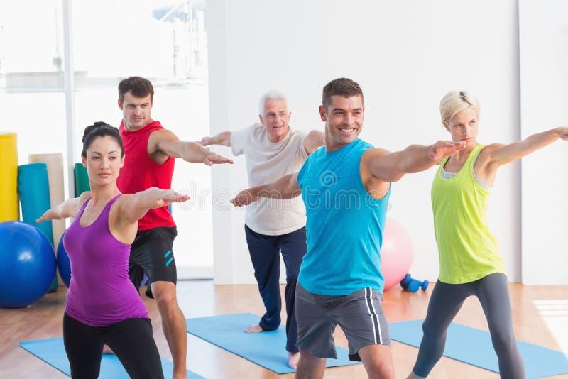 做在瑜伽类的人们战士姿势 免版税库存照片