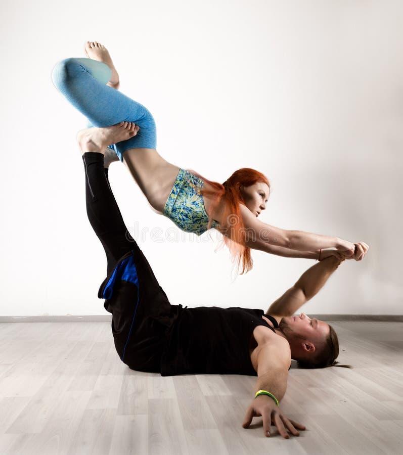 做在瑜伽assanes的人和少妇力量锻炼 Acroyoga概念 免版税图库摄影