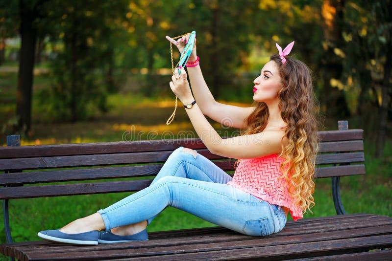 做在电话的女孩的Pin自已在公园 库存照片