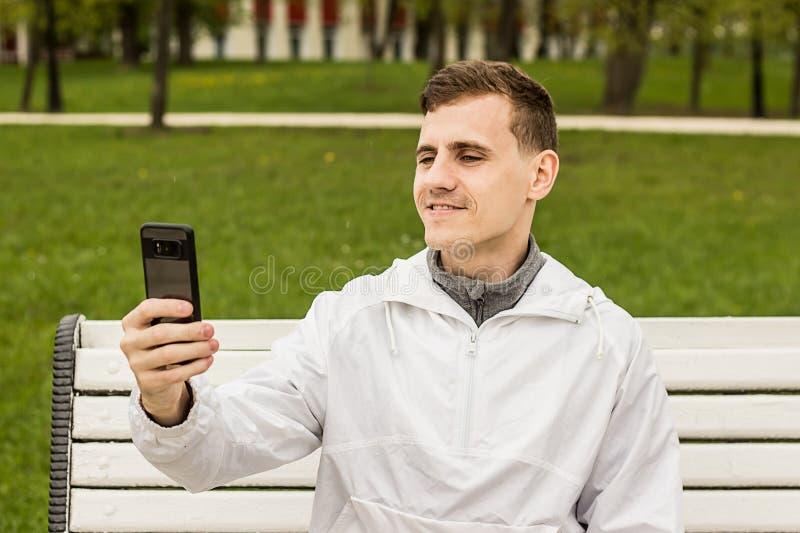 做在电话,图片的可爱selfie的他自己 免版税库存图片