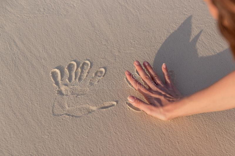 做在白色沙子的年轻女人Handprints 库存图片
