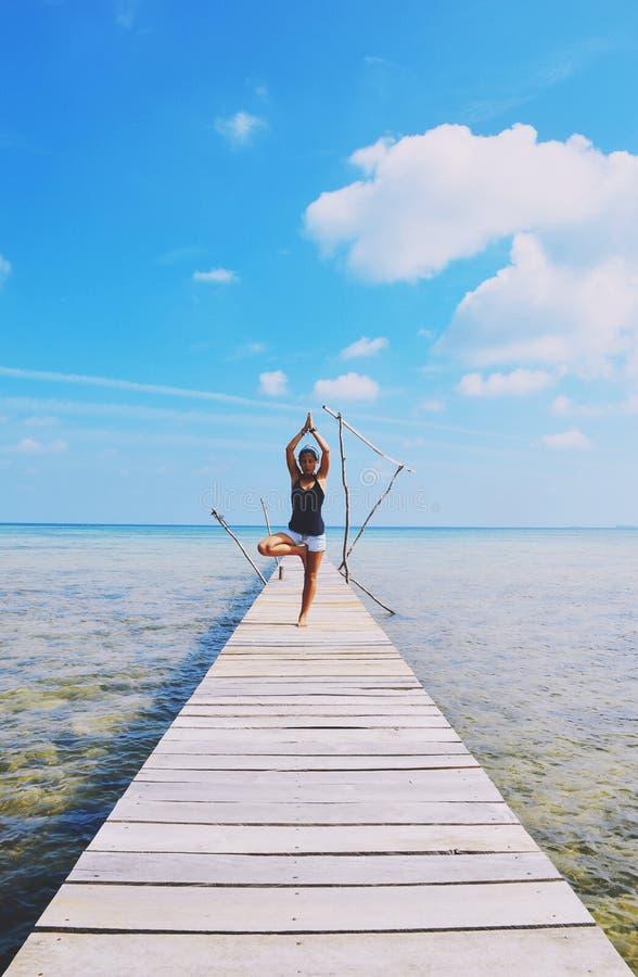 做在码头的热的女孩瑜伽 库存照片