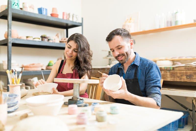 做在碗的微笑的夫妇创造性的绘画在瓦器工作 免版税库存照片